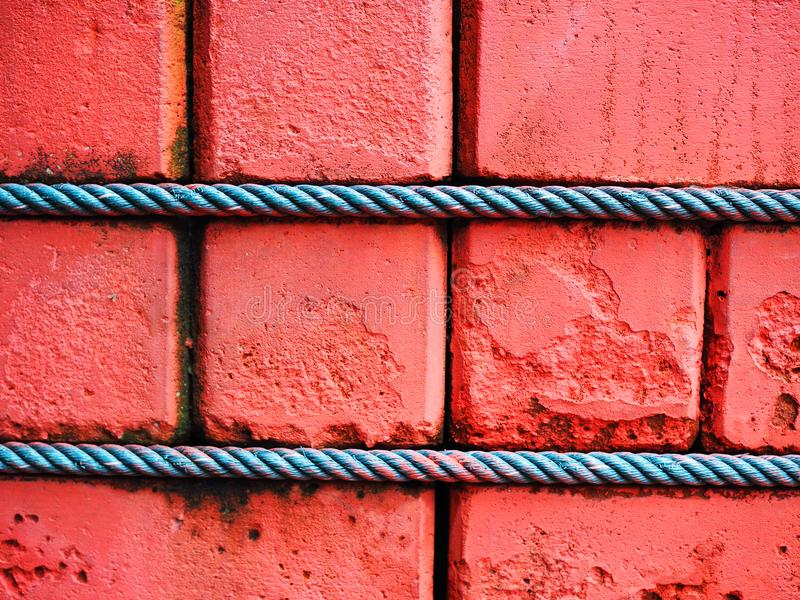 Red clay brick wall with green manila rope tied royalty free stock image