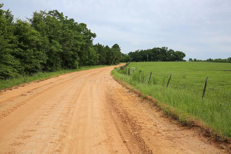 Red clay curved road. Red dirt curved road in rural Georgia, United States of America royalty free stock photography