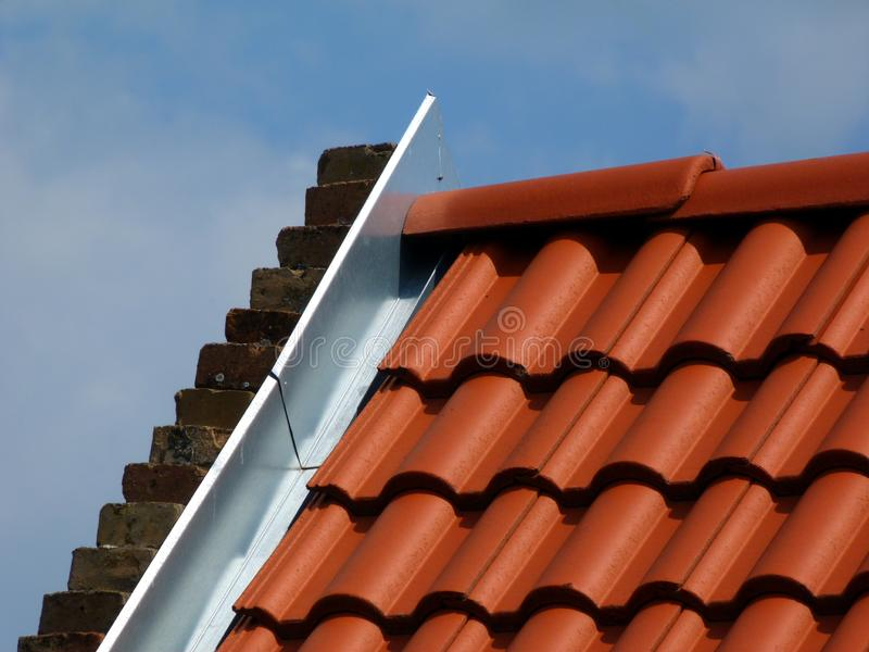 Red clay roof tiles and galvanized metal flashing stock photos