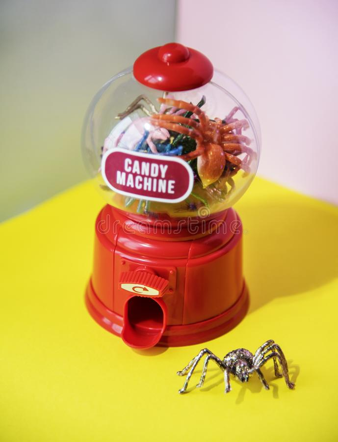 Red and Clear Plastic Candy Machine on Yellow Desk stock photos