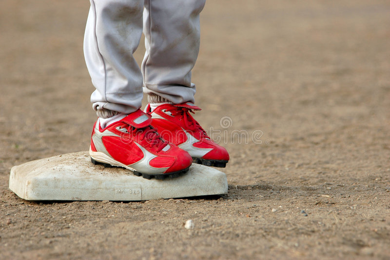 Red Cleats on Base. Close Up of Red Cleats of Base Runner Safe on Second Base After a Steal in Little League stock image