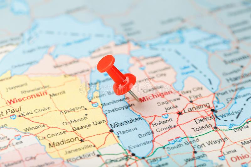 Red clerical needle on a map of USA, Michigan and the capital Lansing. Close up map of Michigan with red tack. United States map pin USA stock photo