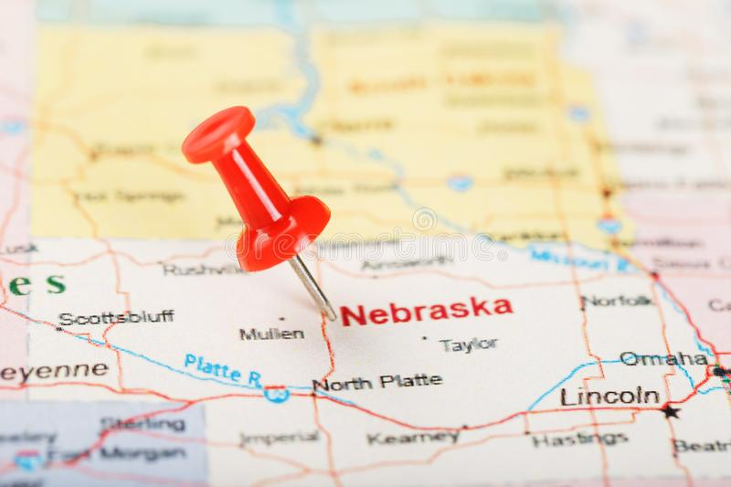 Red clerical needle on a map of USA, Nebraska and the capital Lincoln. Close up map of Nebraska with red tack royalty free stock photo