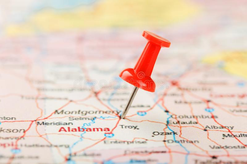 Red clerical needle on a map of USA, South Alabama and the capital Montgomery. Close up map of South Alabama with red tack stock images