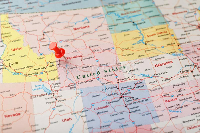 Red clerical needle on a map of USA, Wyoming and the capital Cheyenne. Close up map of wyoming with red tack. US map pin stock photo
