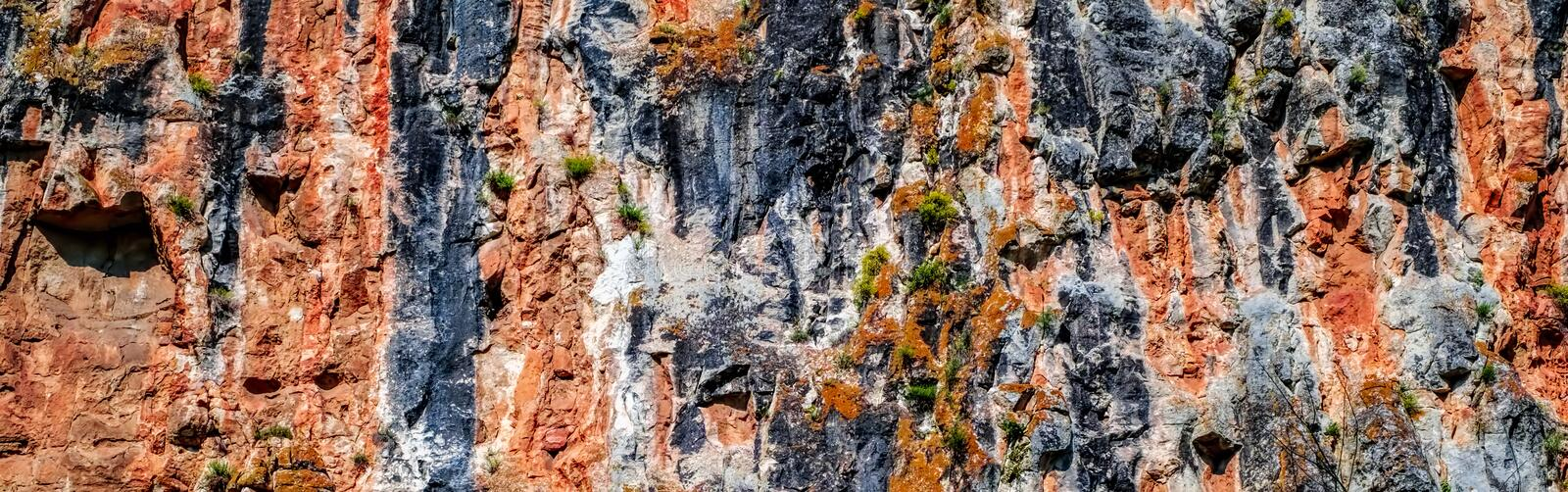 Red cliff wall with clusters of greenery. royalty free stock images