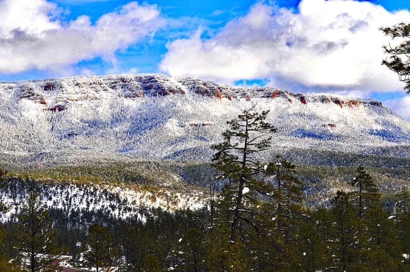 Mountain rim pack with snow pine trees and cloulds. Red cliffs white snow and green pine trees after a snow dump on a wet winter night in Northern Arizona stock images