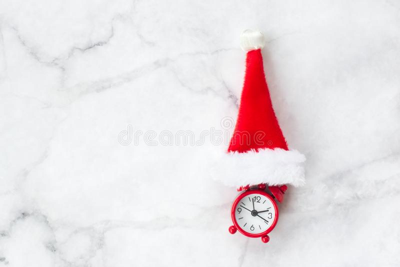 Red clock with red Christmas hat on gray marble background. New Year, Christmas and winter concept. Flat lay, top view, free copy space royalty free stock photography