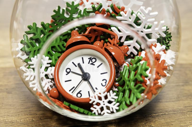 Red clock with colorful snow flakes in glass jar royalty free stock images