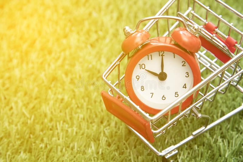 Red clock on the shopping cart, lack of time, waste of time, purchasing time. Offer, table, no, late, timer, buy, white, business, sign, circle, measurement royalty free stock photography