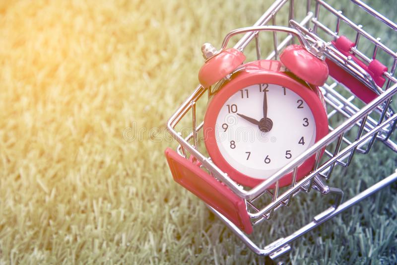 Red clock on the shopping cart, lack of time, waste of time, purchasing time. Offer, table, no, late, timer, buy, white, business, sign, circle, measurement stock photo