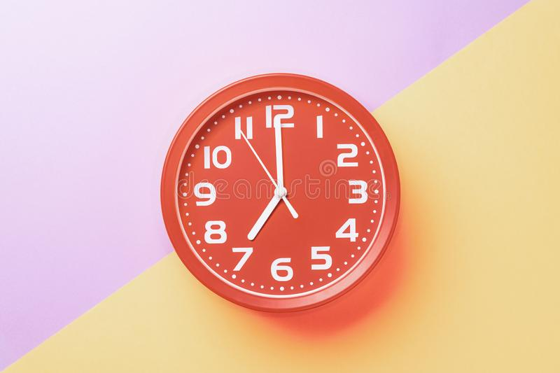 Red clock showing seven o`clock with white numbers on a yellow lilac background.  royalty free stock photo