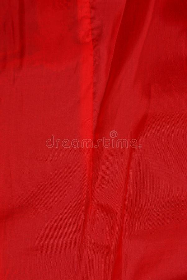 Red fabric texture from a piece of crumpled cloth on clothes. Red cloth background of a piece of crumpled matter on clothes royalty free stock images