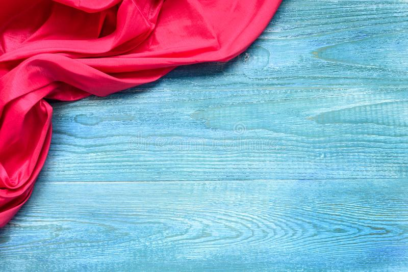Red cloth on a blue wooden table. Copy space and top view. royalty free stock image