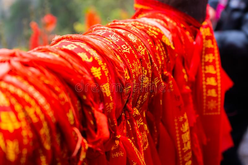 Red cloth charms with Chinese characters are tied up together. A lot of red cloth charms with Chinese characters are tied up together by Chinese and tourists royalty free stock photography