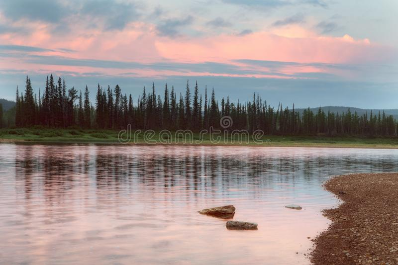 Red clouds over boreal river. royalty free stock photo