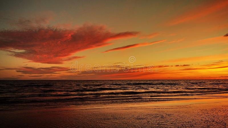 Sunset and red clouds. Red sky and clouds over sea at sunset stock photography