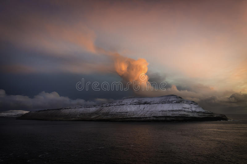 Red clouds on top of islands covered with snow at sunset: Hestur island,Faroe islands, Denmark, Europe royalty free stock image