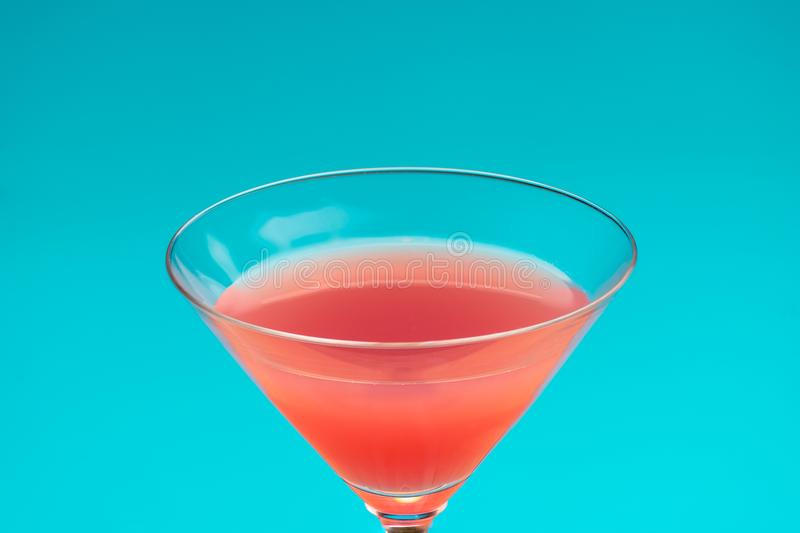 Red cocktail on blue background. refreshing cold drink and Summer vacation royalty free stock image