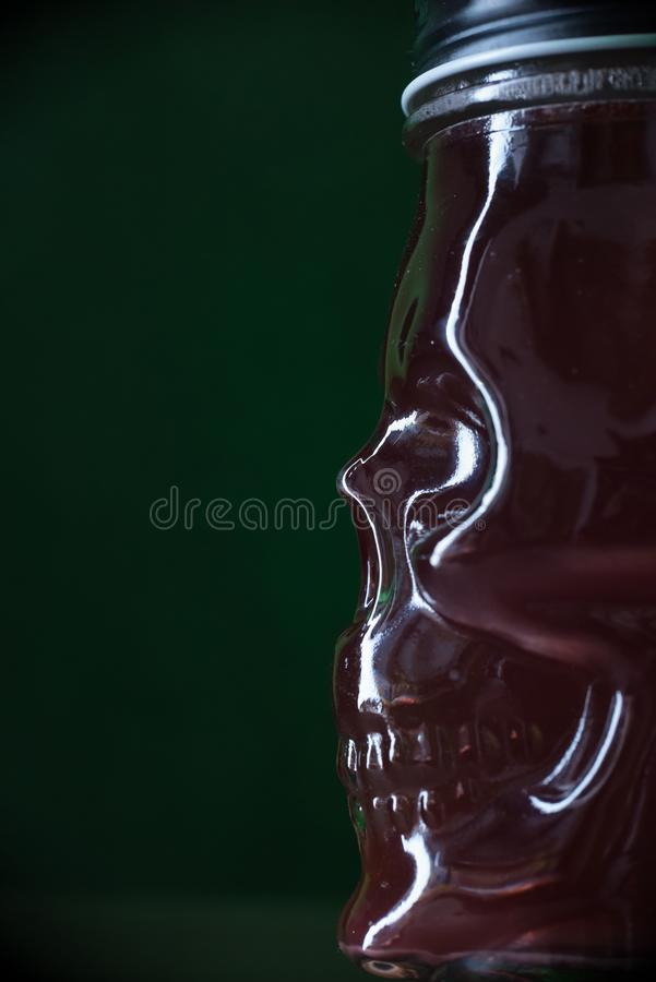 Red cocktail in glass in the form of a skull on green light as a background stock photography