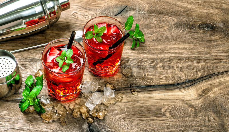 Red cocktail with ice mint leaves on wooden background. Red cocktail with ice, mint leaves and strawberry on wooden background stock photos