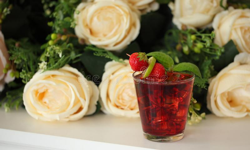 Red cocktail with mint leaf, lime and strawberry, roses on background royalty free stock image