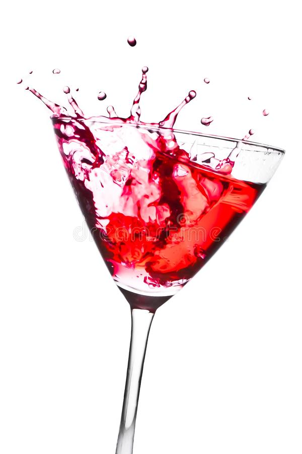 Red cocktail with splashing in the tilted glass. On a white background stock photo