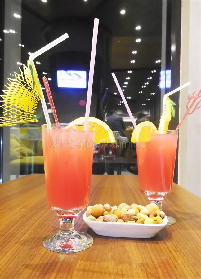Red cocktail with straws, bowl of nuts, holiday, Alanya, Turkey, orange slices, stock photography