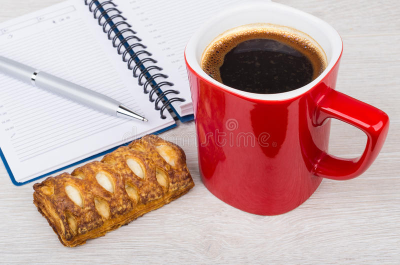 Red coffee cup, cookie, notepad and ball point pen. On wooden table stock image