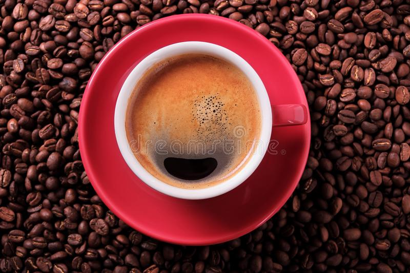 Red coffee cup with espresso and roasted beans closeup. Red coffee cup with espresso and roasted beans royalty free stock images