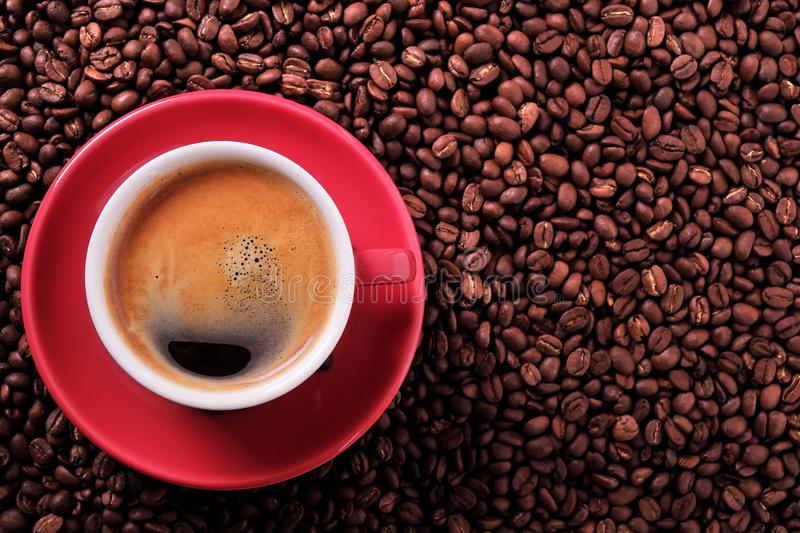 Red coffee cup with espresso and roasted beans closeup. Red coffee cup with espresso and roasted beans royalty free stock photo