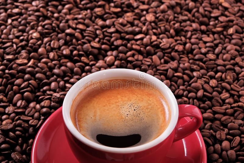 Red coffee cup with espresso and roasted beans closeup. Red coffee cup with espresso and roasted beans stock photo