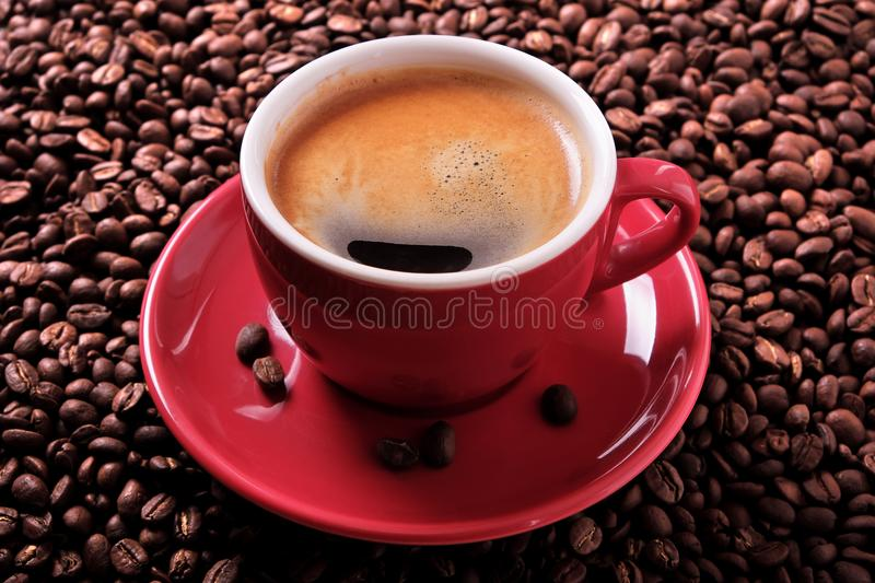 Red coffee cup with espresso and roasted beans close up. Red coffee cup with espresso and roasted beans closeup royalty free stock images