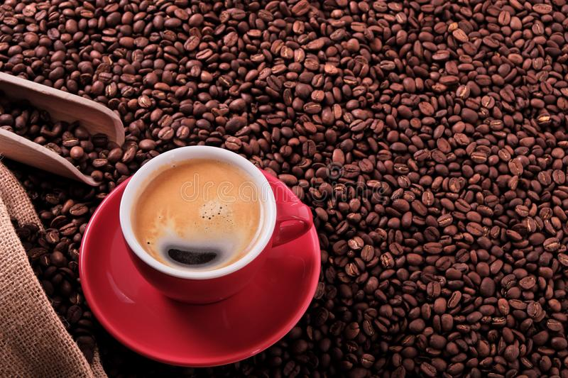 Red coffee cup with espresso and roasted beans background. Red coffee cup with espresso and roasted beans stock photography