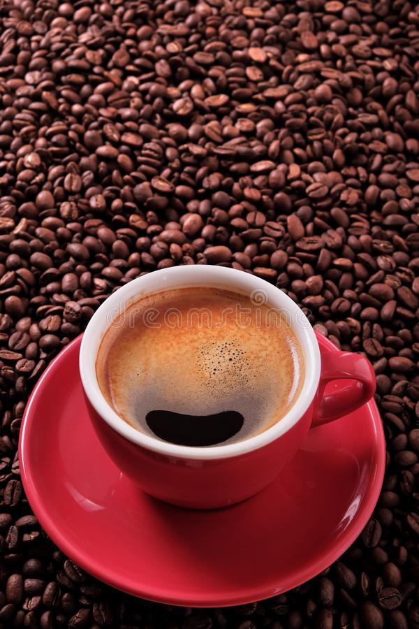 Red coffee cup with espresso and roasted beans vertical. Red coffee cup with espresso and roasted beans stock photo