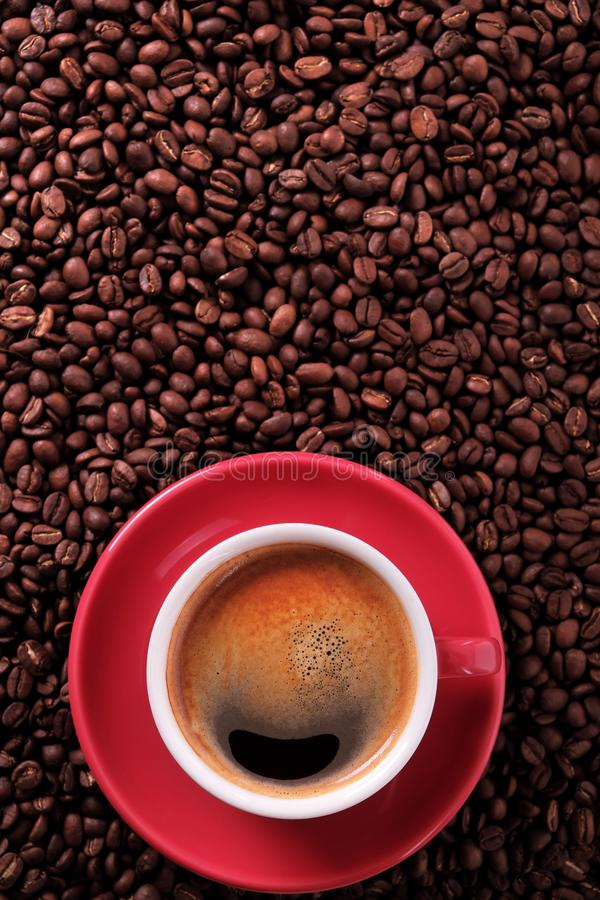 Red coffee cup with espresso and roasted beans vertical copy space. Red coffee cup with espresso and roasted beans vertical stock photography