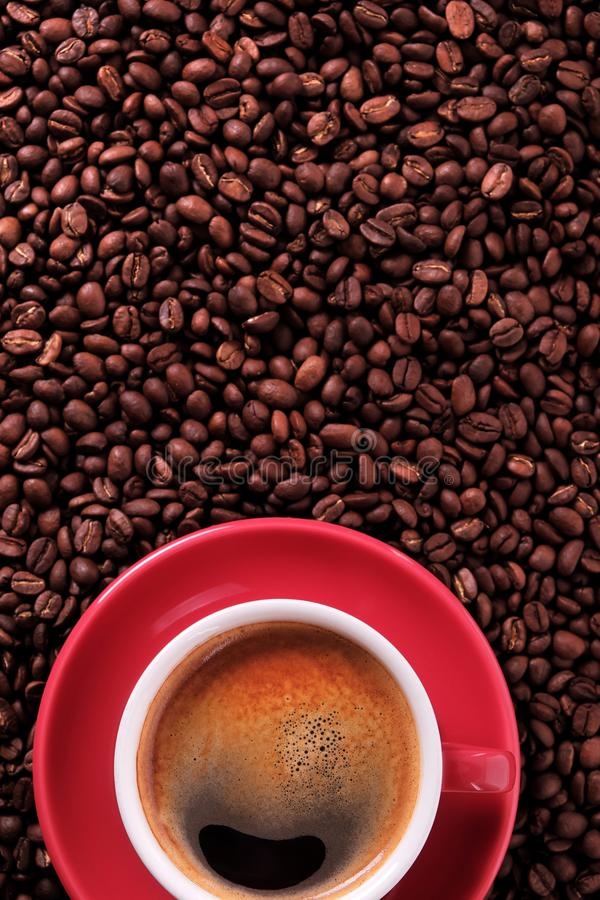 Red coffee cup with espresso and roasted beans vertical. Copy space royalty free stock photography