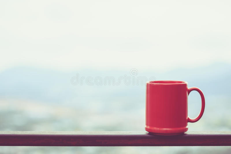Red coffee cup on terrace and blur view of city background stock photography