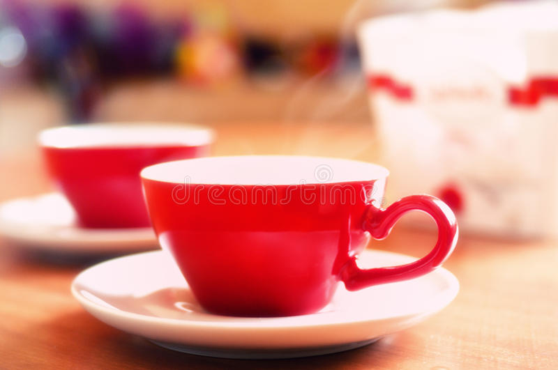 Red Coffee or Tea Cups. Two red coffee or tea cups with white saucers on a table stock photography