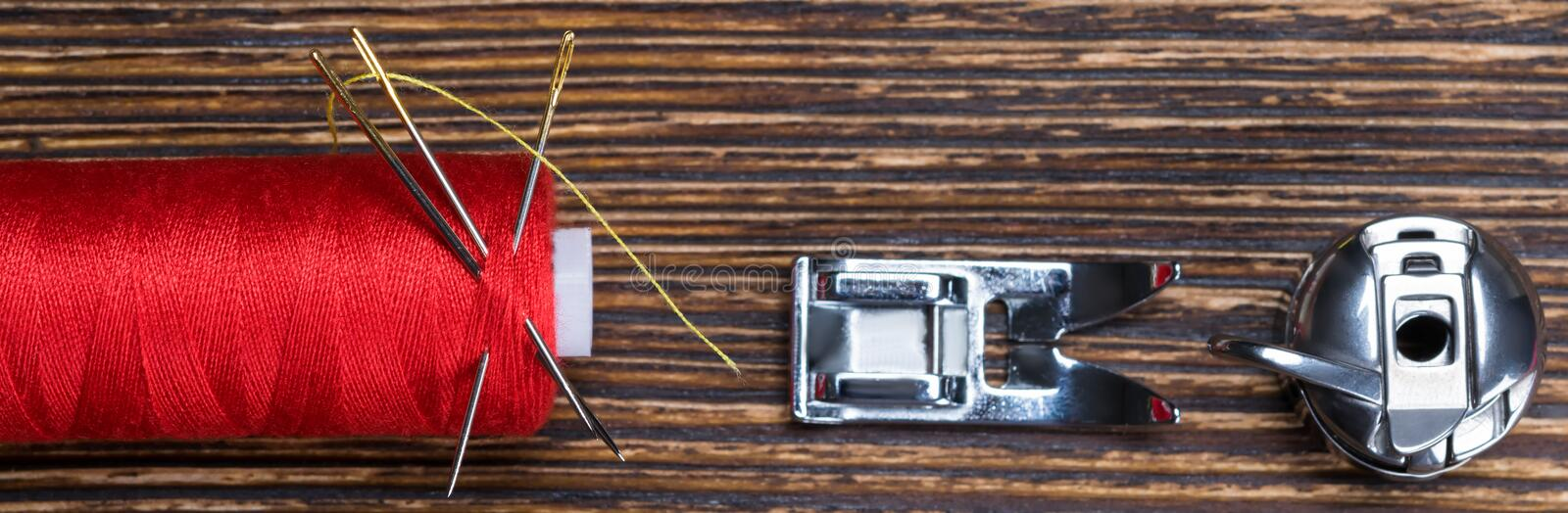 Red coil thread on a wooden background, with a set of spare parts for a sewing machine stock image