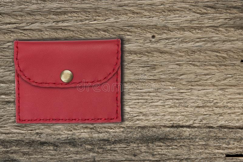 Red coin purse on wooden texture for background stock images