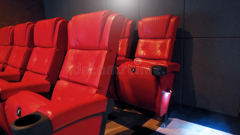 Red color leather movie theater cinema seat chairs. Red color leather movie theater cinema seat chairs which small and old dirty and very bad stingy smell royalty free stock photography