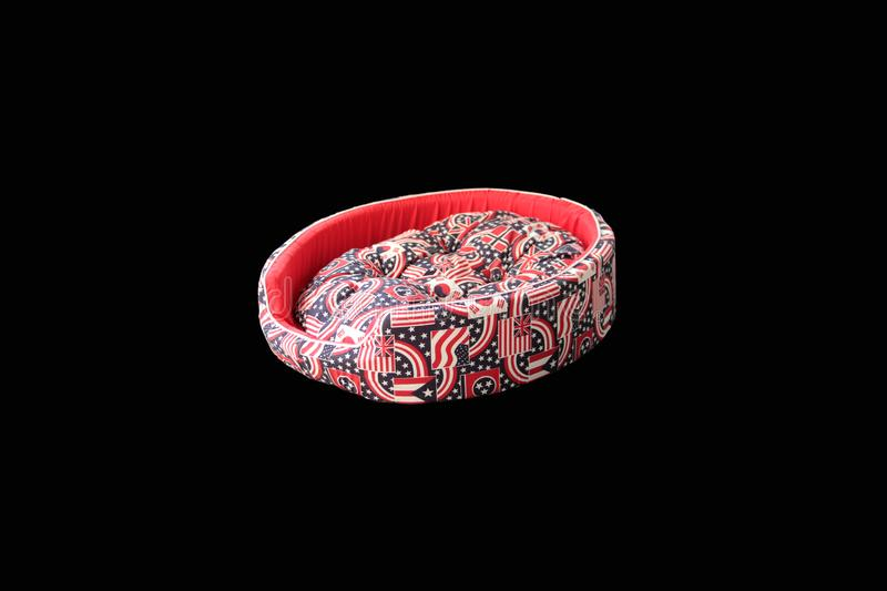 Red color pet bed on black background isolated. Pet supplies stock image