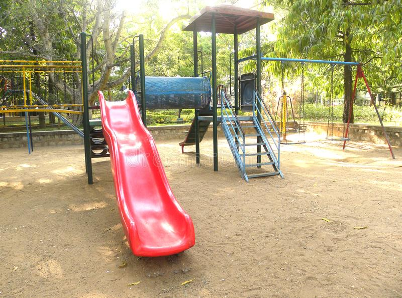 Red color slide at playground for children royalty free stock photography