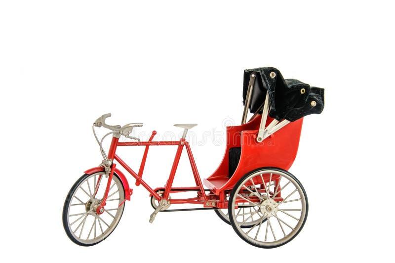 Red color vintage oriental rickshaw cab, miniature stock photography