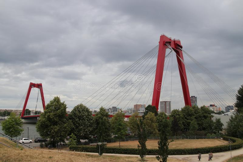 Red colored bridge in Rotterdam named Willemsbrug in the center of Rotterdam over river Nieuwe Maas royalty free stock photos