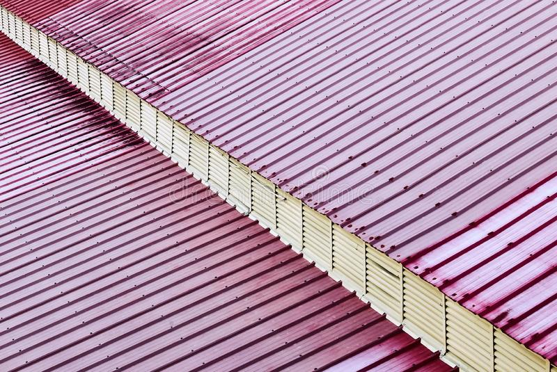 Red colored metal sheet roofing with a white diagonal line stock photography
