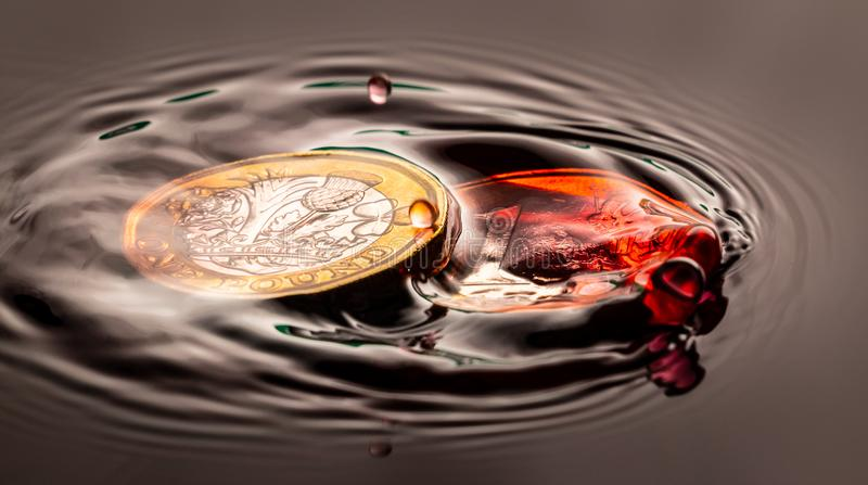 Red water drop falling and splashing on a coin stock photos
