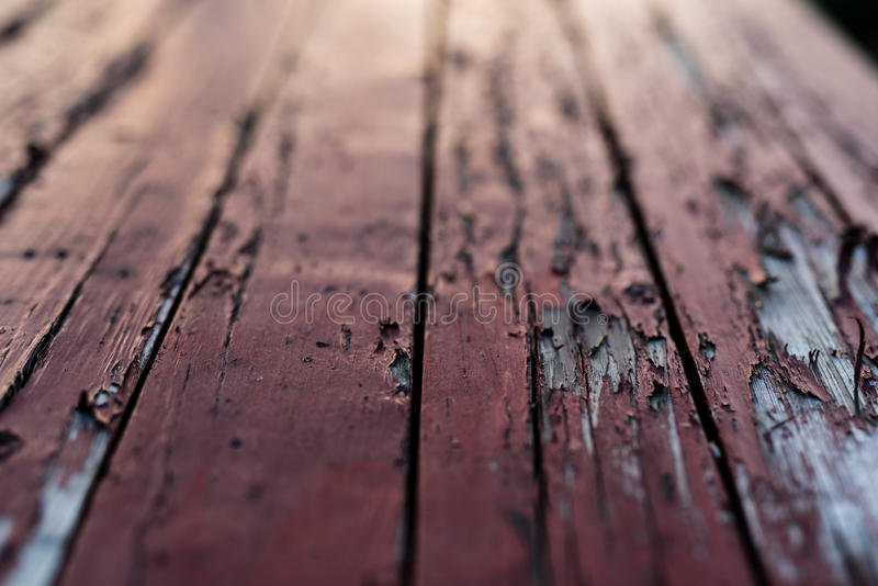 Red colored wooden floor with red paint starting to peel off. Shallow depth of field royalty free stock photos
