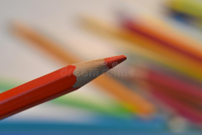 Red coloured pencil. On colourful background stock photo